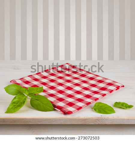 Red checkered napkin and leaves on table over vintage background - stock photo