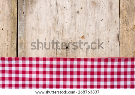 Red checkered tablecloth on a rustic wooden background - stock photo