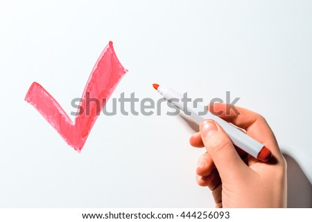red checkmark on the blackboard and hand with marker makes a choice - stock photo