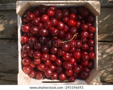 red cherries in a square wooden box, packed to deliver, on natural rustic wooden board background, in garden environment, topview - stock photo