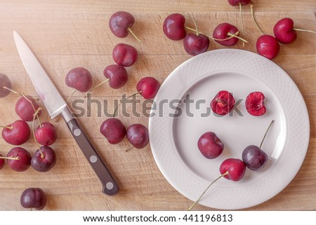 red cherry fruit spreads on a cutting board with a white plate and a small knife. Red cherries on a wooden board background (cherry fruit) remark: cherry cherry cherry cherry cherry cherry cherry  - stock photo
