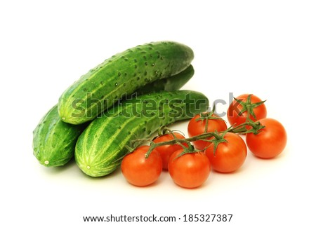 Red cherry tomatoes and green cucumbers - stock photo