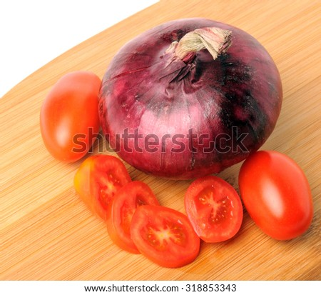 red cherry tomatoes and red onion on Bamboo cutting board - stock photo