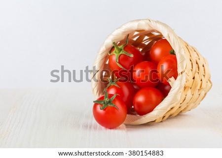 Red cherry tomatoes in a woven basket on a white background - stock photo