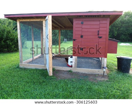 red chicken coop made of wood and screen    - stock photo