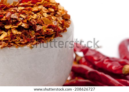 Red Chili Pepper Flakes in white granite pestle; mortar and scattered Red Chili Peppers; isolated on white background - stock photo