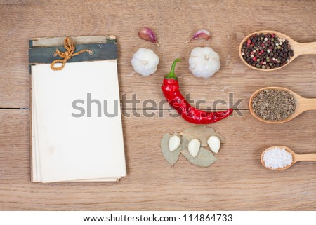 Red chili pepper, garlic, bay leaf, spices in spoons, old notebook on oak wood texture background - stock photo