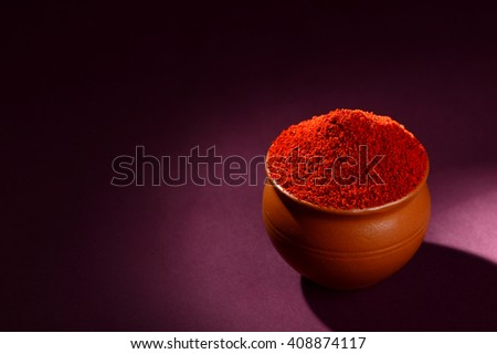 Red Chili Pepper powder in clay pot on dark background - stock photo