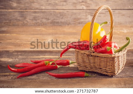 red chili peppers in basket on old wooden table - stock photo