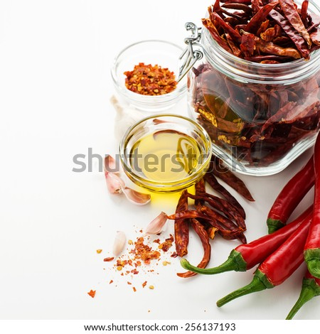 Red Chili Peppers with herbs and spices over white background - stock photo