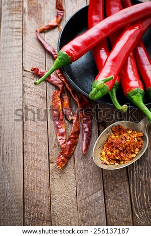 Red Chili Peppers with herbs and spices over wooden background - stock photo