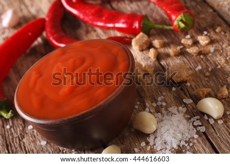 Red chilli sauce Sriracha with ingredients on the table. horizontal, macro