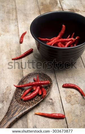 red chilli with kitchen utensils for cooking on the wood table - stock photo