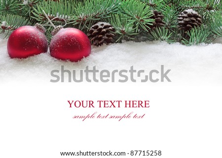 Red christmas balls and branch of fir tree  in snow isolated on the white background. - stock photo