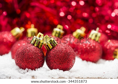 Red Christmas balls on snow against red bokeh background. - stock photo