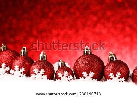 red christmas balls on snow. studio shot - stock photo