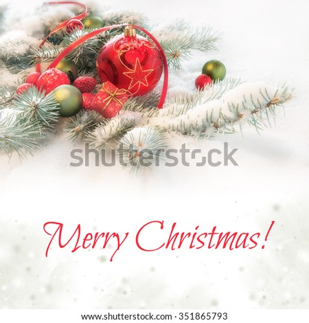 """Red Christmas bauble on decorated fir twigs in snow, caption """"Merry Christmas"""" on abstract background.  - stock photo"""