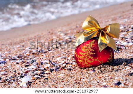 Red christmas bauble with golden bow on the sand against blue ocean - stock photo