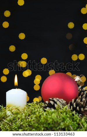 Red Christmas baubles and candle on black background of defocused golden lights. - stock photo