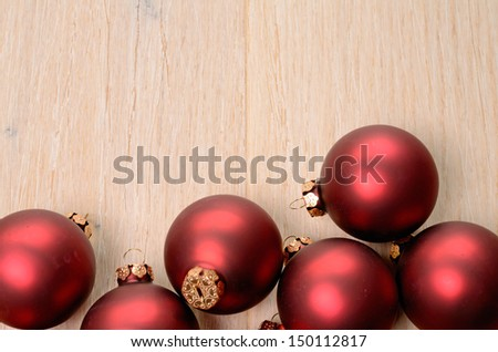 Red Christmas baubles on a wooden background with space for your text - stock photo