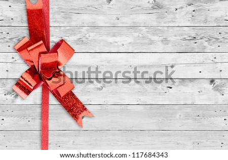 Red Christmas bow on grunge wooden background with space for text - stock photo