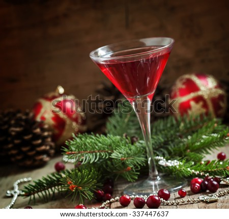Red Christmas cocktail in a martini glass with fir branches, pine cones and Christmas balls on the old wooden background, selective focus - stock photo