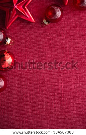Red christmas decorations (stars and balls) on red canvas background. Merry christmas card. Winter holidays. Xmas theme. Space for text. Happy New Year. - stock photo