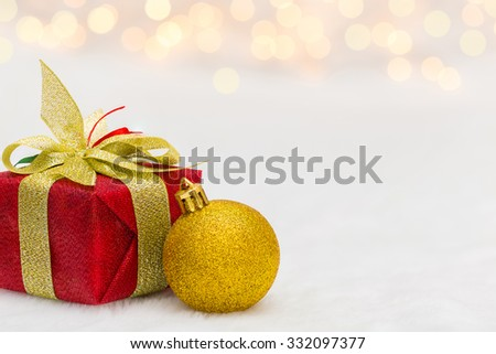 Red Christmas gift box with shiny golden ball. Bokeh with glow effect on white background. Copyspace for your greeting or wishes - stock photo
