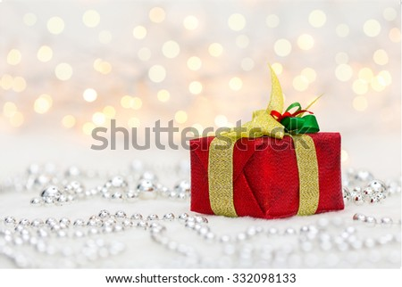 Red Christmas gift box with shiny golden ribbon and metallic beads. Bokeh with glow effect on white background. Copyspace for your greeting or wishes - stock photo