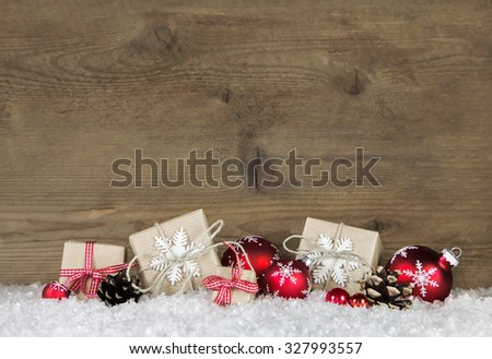 Red Christmas gifts wrapped in natural paper on old wooden grey background. - stock photo