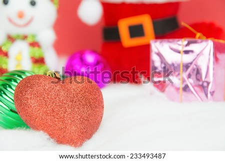 Red christmas heart and Snow man and Santa boots with gift on white snow on red background, concept christmas and Valentine day - stock photo