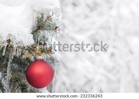 Red Christmas ornament hanging on snow covered spruce tree outside with copy space - stock photo