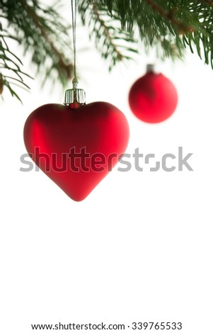 Red christmas ornaments (heart and ball) on the xmas tree on white background isolated. Merry christmas card. Winter holidays. Xmas theme. - stock photo