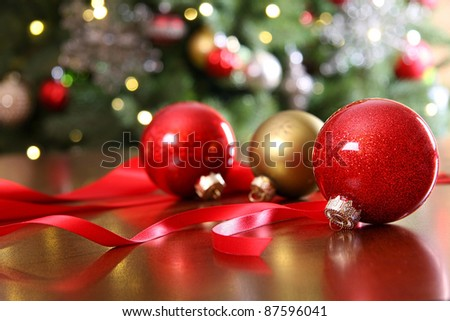 Red Christmas ornaments on a table with  decorated tree in  background. - stock photo