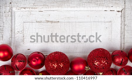 Red Christmas ornaments on antique cracked wood panel - stock photo