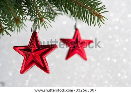 Red christmas ornaments (stars) on the xmas tree on glitter bokeh background. Merry christmas card. Winter holidays. Xmas theme. - stock photo