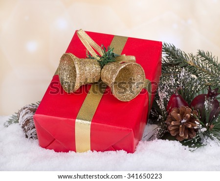 Red Christmas present on snow with holiday background - stock photo