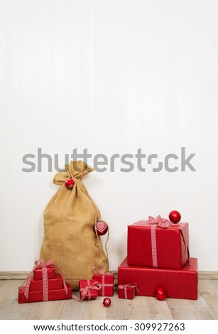 Red christmas presents with santa sack on white wooden wall for decoration. - stock photo