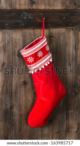 red christmas sock with snowflakes for Santa gifts hanging on wooden background. holidays symbol stocking - stock photo
