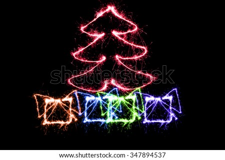 red Christmas tree and gifts made by sparkler on a black background - stock photo