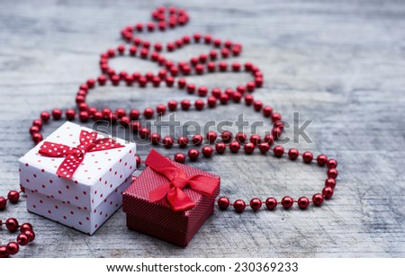 Red Christmas tree made of red pearls decoration and gift boxes under the tree  - stock photo