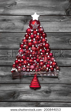 Red christmas tree with balls on old wooden shabby background. - stock photo