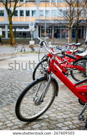 Red city bikes for rent on rainy day in Hamburg,  Germany. Selective focus. - stock photo