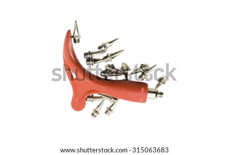 Red cleat wrench and replacement track needle spikes isolated on white background - stock photo