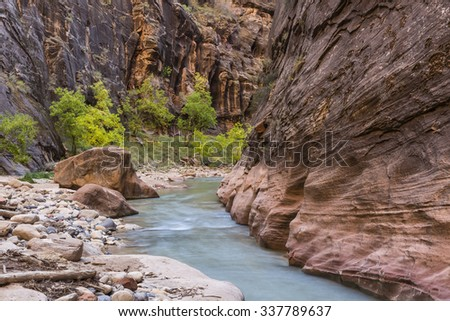 Red cliffs flank the blue river of the Virgin Narrows slot canyon in Zion National Park, Utah. - stock photo