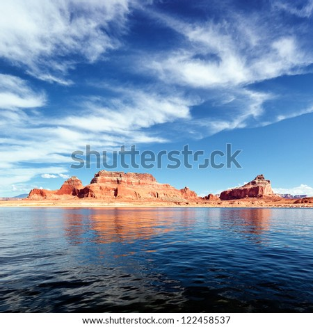 red cliffs reflected in the water of the lake Powell - stock photo