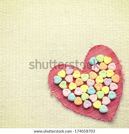 Red Cloth Valentine with Heart Shaped Candies in the center.  Aged yellow cardboard background with room or space for copy, text, words - stock photo