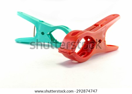 Red clothespin with blurred green clothespin isolated on white background - stock photo