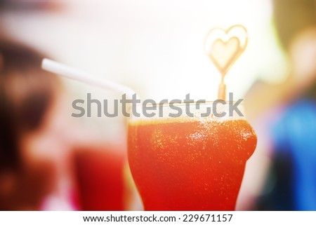 Red cocktail in funny glass in the shape of female breast. Vintage color effect. - stock photo