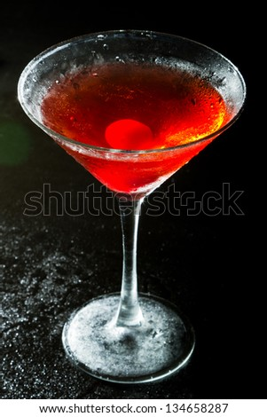 red cocktail on a dark background fading in to black garnished with a red cherry - stock photo